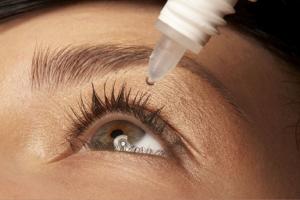 Woman putting eye drops in her eye