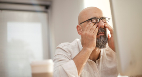 Man with glasses rubbing his eyes
