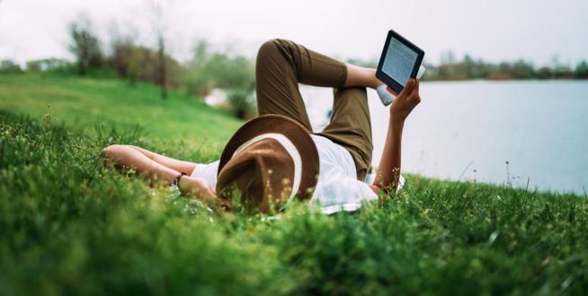 Man-lying-on-grass-reading