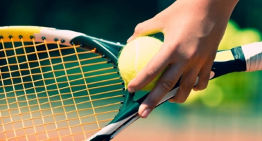Hand holding a tennis racket and a ball