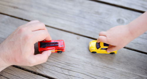 Hands playing with toy cars