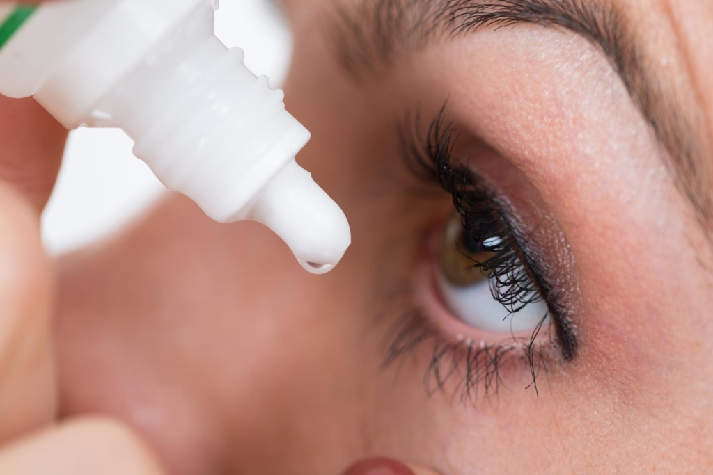 Women dropping eye's liquid on her eye